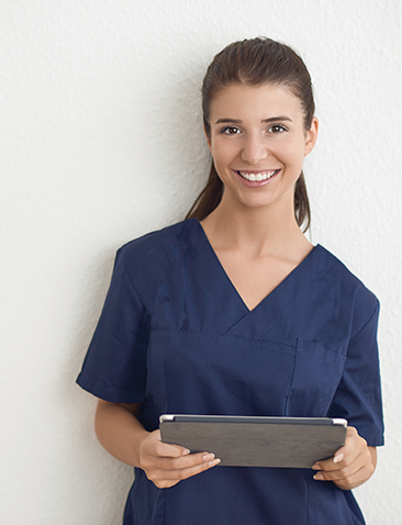 Female healthcare professional closeup smiling at the camera holding documents.